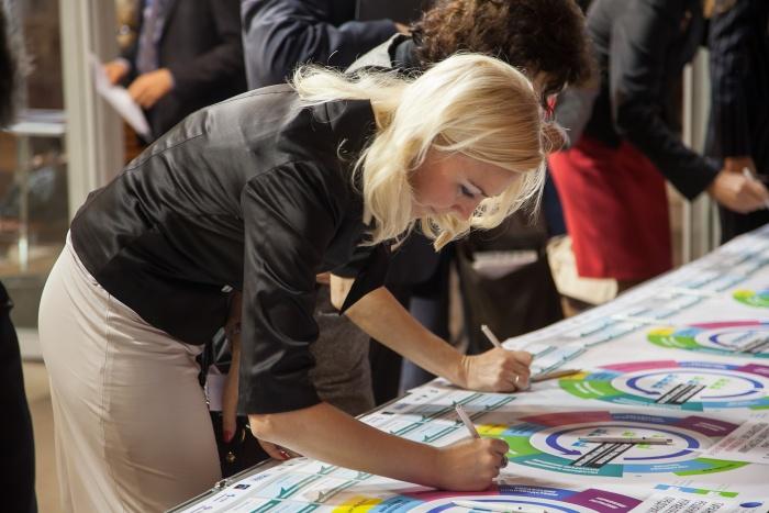 участники стартового совещания по проекту SAP ERP записывают на плакате свои пожелания удачи коллегам в достижении поставленных целей